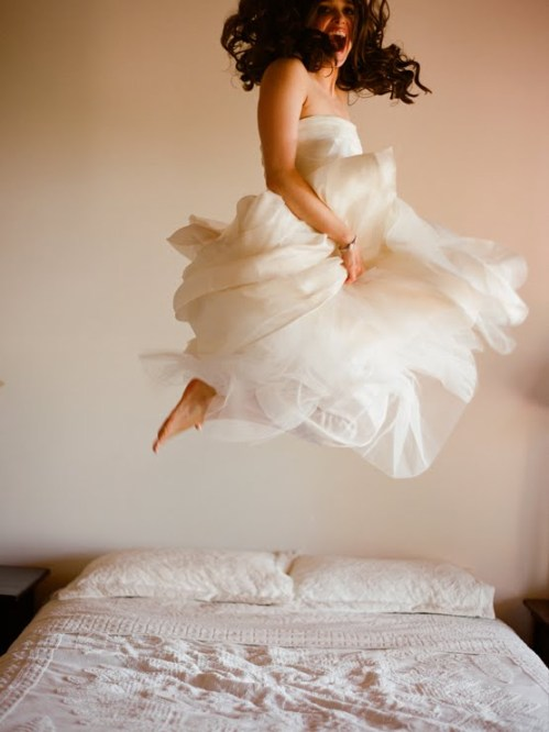 Happy bride jumping on a bed_photo by Elizabeth Messina