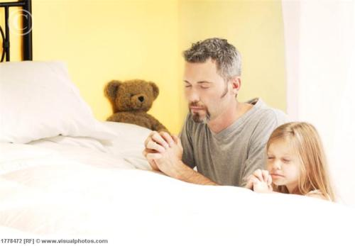 Father praying with daughter